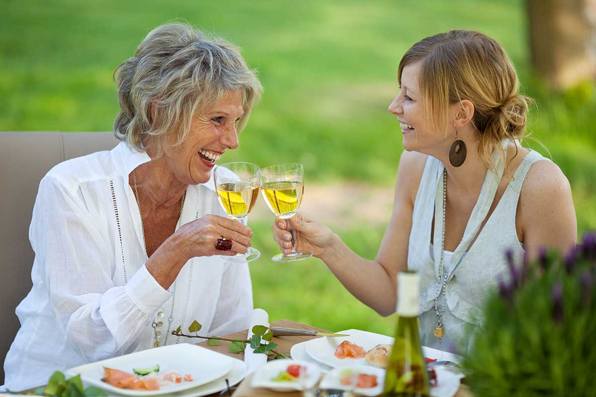 mother and daughter sipping wine