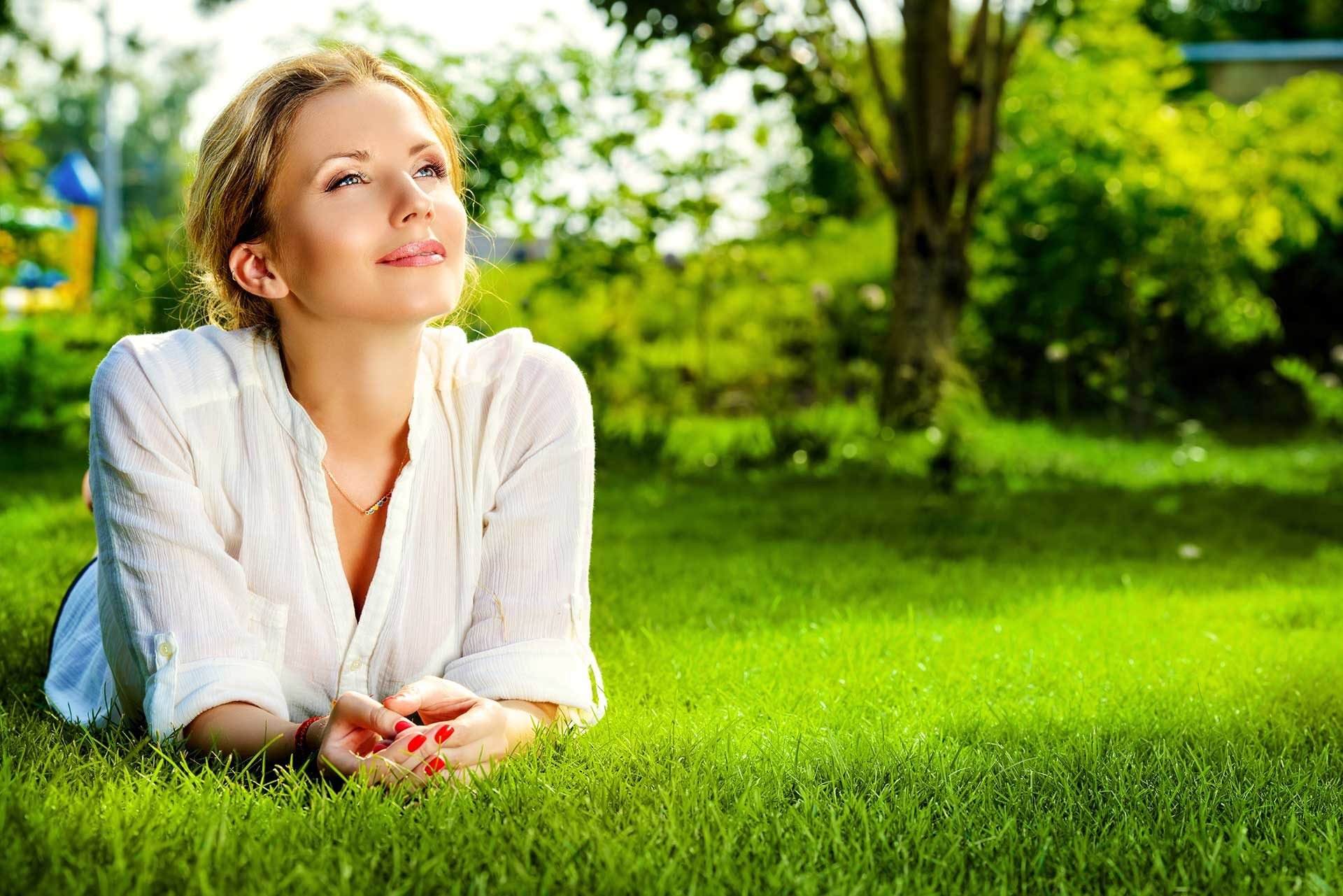 blonde holistic dental patient enjoying laying in grass